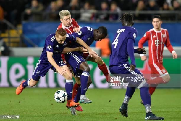 Anderlecht's French midfielder Adrien Trebel and Anderlecht's French defender Dennis Appiah vie with Bayern Munich's Polish forward Robert...