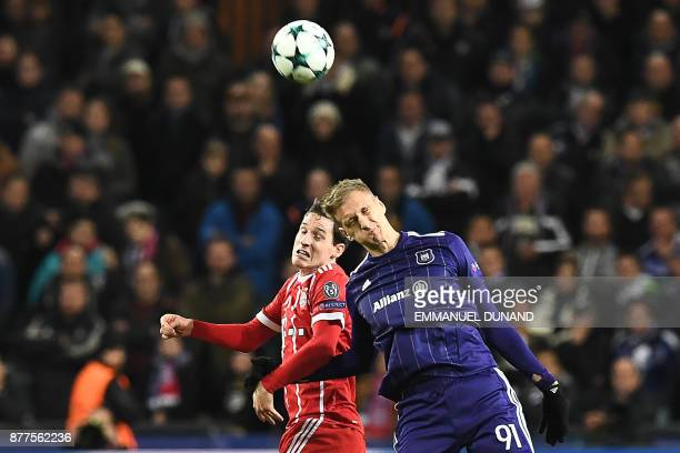 Anderlecht's Polish forward Lukasz Teodorczyk heads the ball with Bayern Munich's German midfielder Sebastian Rudy during the UEFA Champions League...