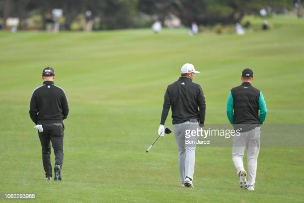 Anders Albertson Wyndham Clark and Sam Burns walk down the seventh hole fairway together during the first round of The RSM Classic at the Sea Island...