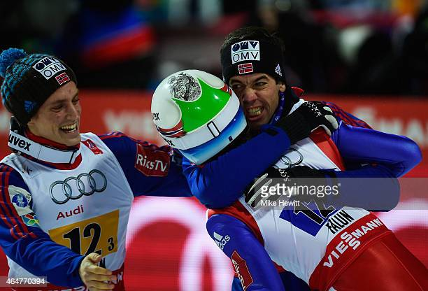 Anders Bardal and Anders Fannemel of Norway congratulate Rune Velta as they win the gold medal in the Men's Team HS134 Large Hill Ski Jumping during...
