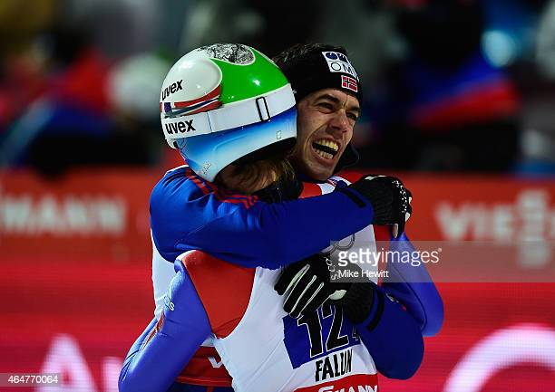 Anders Bardal of Norway congratulates Rune Velta of Norway as they win the gold medal in the Men's Team HS134 Large Hill Ski Jumping during the FIS...