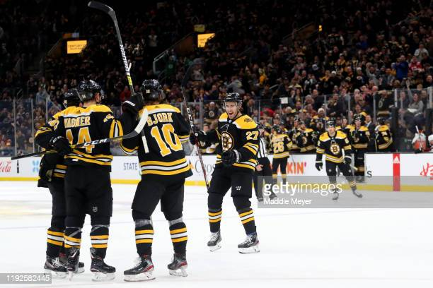 Anders Bjork and John Moore celebrate with Chris Wagner of the Boston Bruins safter he scored a goal against the Colorado Avalanche during the first...
