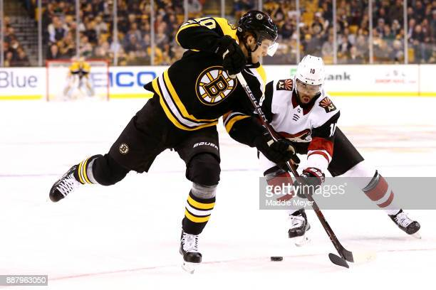 Anders Bjork of the Boston Bruins and Anthony Duclair of the Arizona Coyotes battle for control of the puck during the first period at TD Garden on...