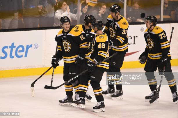 Anders Bjork of the Boston Bruins celebrates his goal with his line mates against the Arizona Coyotes at the TD Garden on December 7 2017 in Boston...