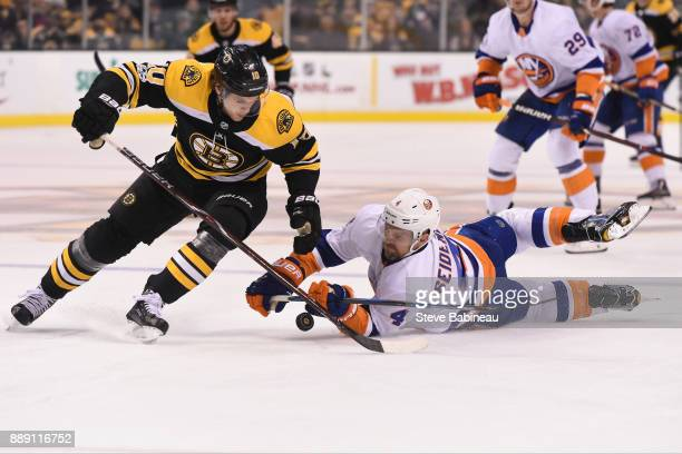Anders Bjork of the Boston Bruins fights for the puck against Dennis Seidenberg of the New York Islanders at the TD Garden on December 9 2017 in...