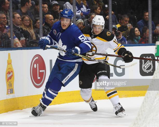Anders Bjork of the Boston Bruins hits Jake Gardiner of the Toronto Maple Leafs at the Air Canada Centre on November 10 2017 in Toronto Canada The...