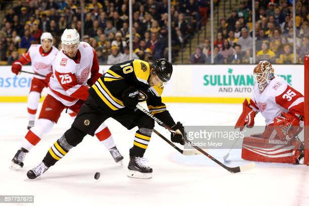 Anders Bjork of the Boston Bruins looks for a shot against Jimmy Howard of the Detroit Red Wings during the third period at TD Garden on December 23...