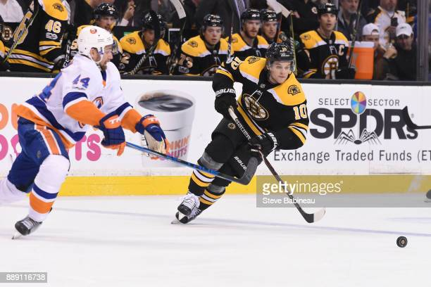 Anders Bjork of the Boston Bruins skates after the puck against Thomas Hickey of the New York Islanders at the TD Garden on December 9 2017 in Boston...