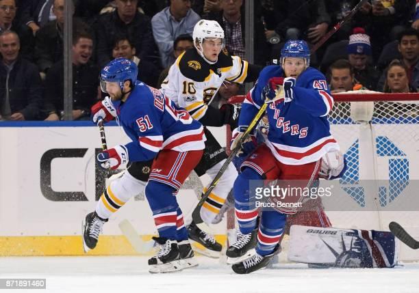 Anders Bjork of the Boston Bruins skates against David Desharnais and Steven Kampfer of the New York Rangers at Madison Square Garden on November 8...