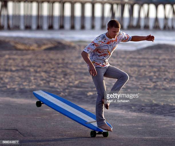 Anders Hamborg hangs five while crossing his legs a move that complements his surfing style on a 6'8' long Hamboard skateboard along the Huntington...
