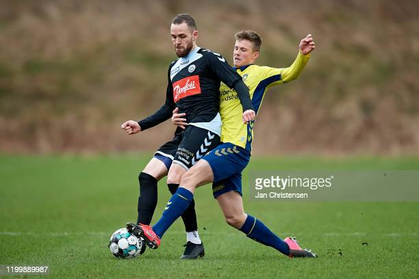 Anders K. Jacobsen of SonderjyskE and Morten Frendrup of Brondby IF compete for the ball during the testmatch between Brondby IF and SonderjyskE at...
