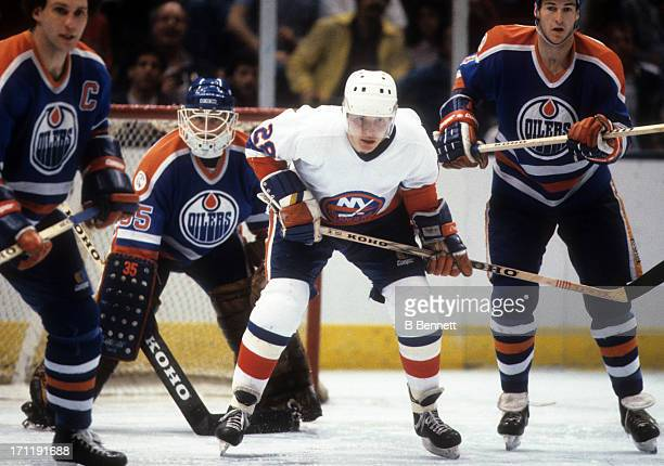 Anders Kallur of the New York Islanders is defended by Lee Fogolin Kevin Lowe and goalie Andy Moog of the Edmonton Oilers during the 1984 Stanley Cup...