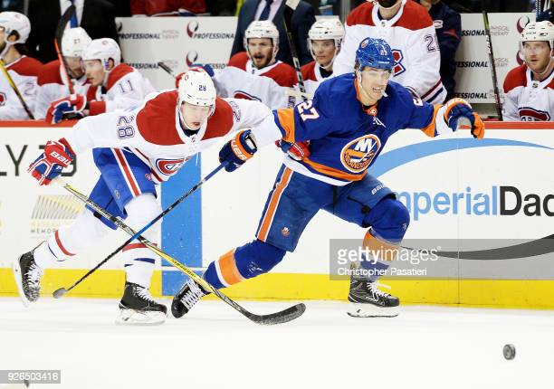 Anders Lee of the New York Islanders and Mike Reilly of the Montreal Canadiens chase down a loose puck during the first period at Barclays Center on...