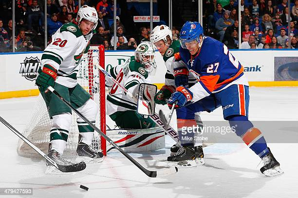 Anders Lee of the New York Islanders battles for the puck with Ryan Suter of the Minnesota Wild at Nassau Veterans Memorial Coliseum on March 18 2014...