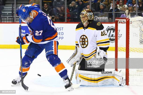 Anders Lee of the New York Islanders deflects a puck in front of Tuukka Rask of the Boston Bruins during the first period at Barclays Center on...