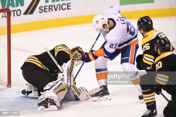 Anders Lee of the New York Islanders fight for the loose puck against Tuukka Rask of the Boston Bruins at the TD Garden on December 9 2017 in Boston...