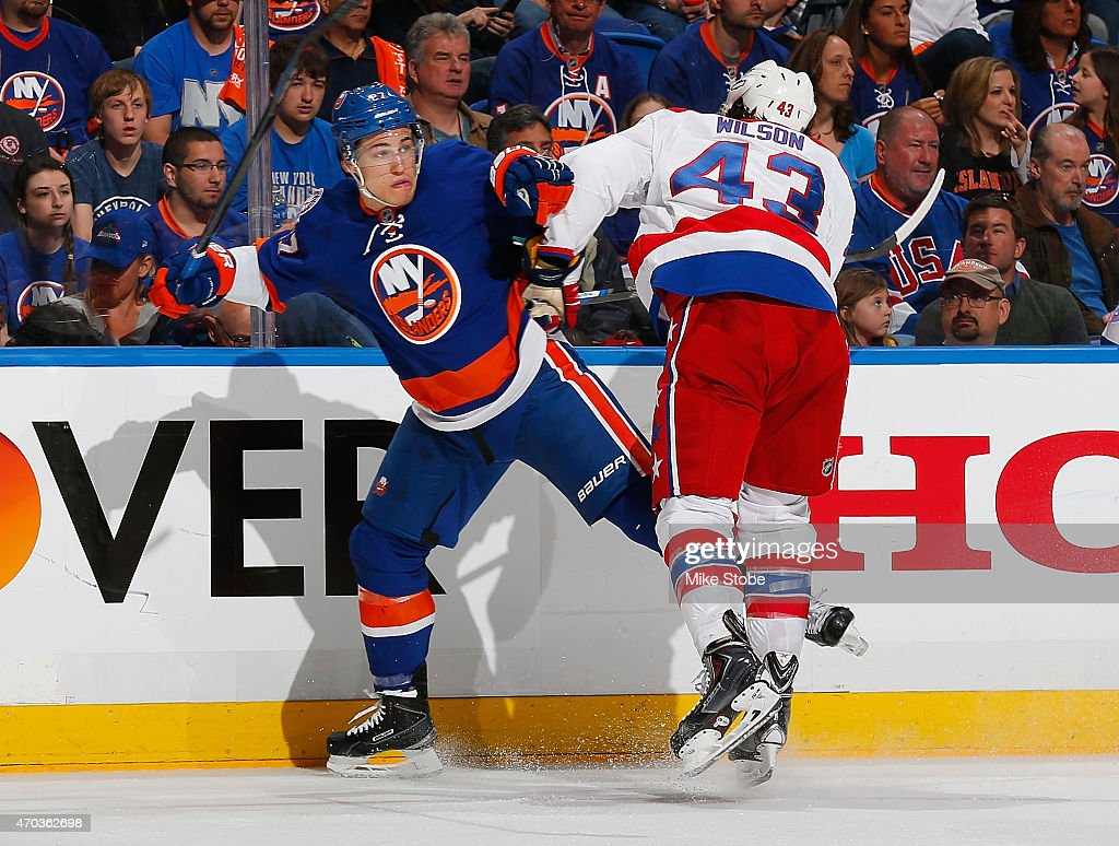 Anders Lee #27 of the New York Islanders is checked by Tom Wilson #43 of the Washington Capitals during Game Three of the Eastern Conference Quarterfinals during the 2015 NHL Stanley Cup Playoffs at Nassau Veterans Memorial Coliseum on April 19, 2015 in Uniondale, New York.