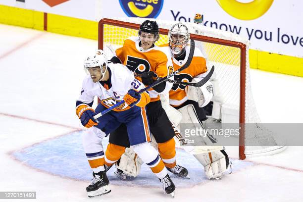 Anders Lee of the New York Islanders is checked by Travis Sanheim of the Philadelphia Flyers in front of Carter Hart during the third period in Game...