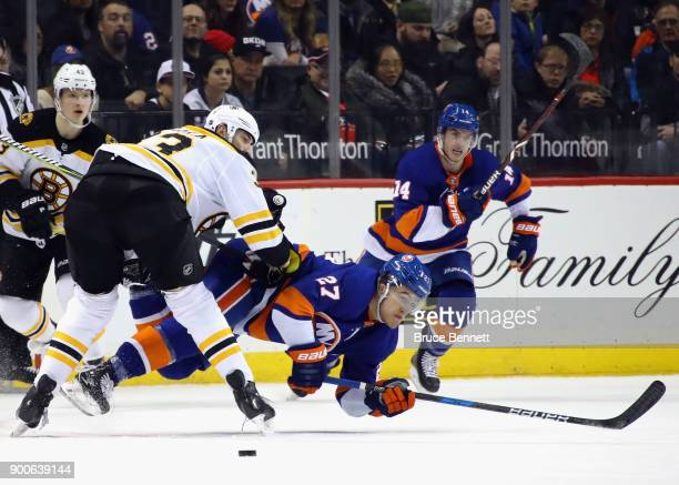 Anders Lee of the New York Islanders is checked by Zdeno Chara of the Boston Bruins during the second period at the Barclays Center on January 2,...
