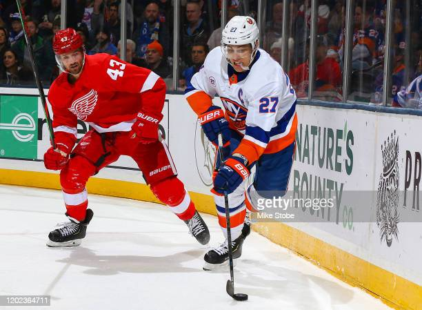 Anders Lee of the New York Islanders is defended by Darren Helm of the Detroit Red Wings during the first period at NYCB Live's Nassau Coliseum on...