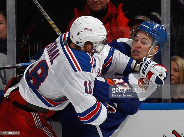 Anders Lee of the New York Islanders is hit into the boards by Marc Staal of the New York Rangers during the third period at the Nassau Veterans...