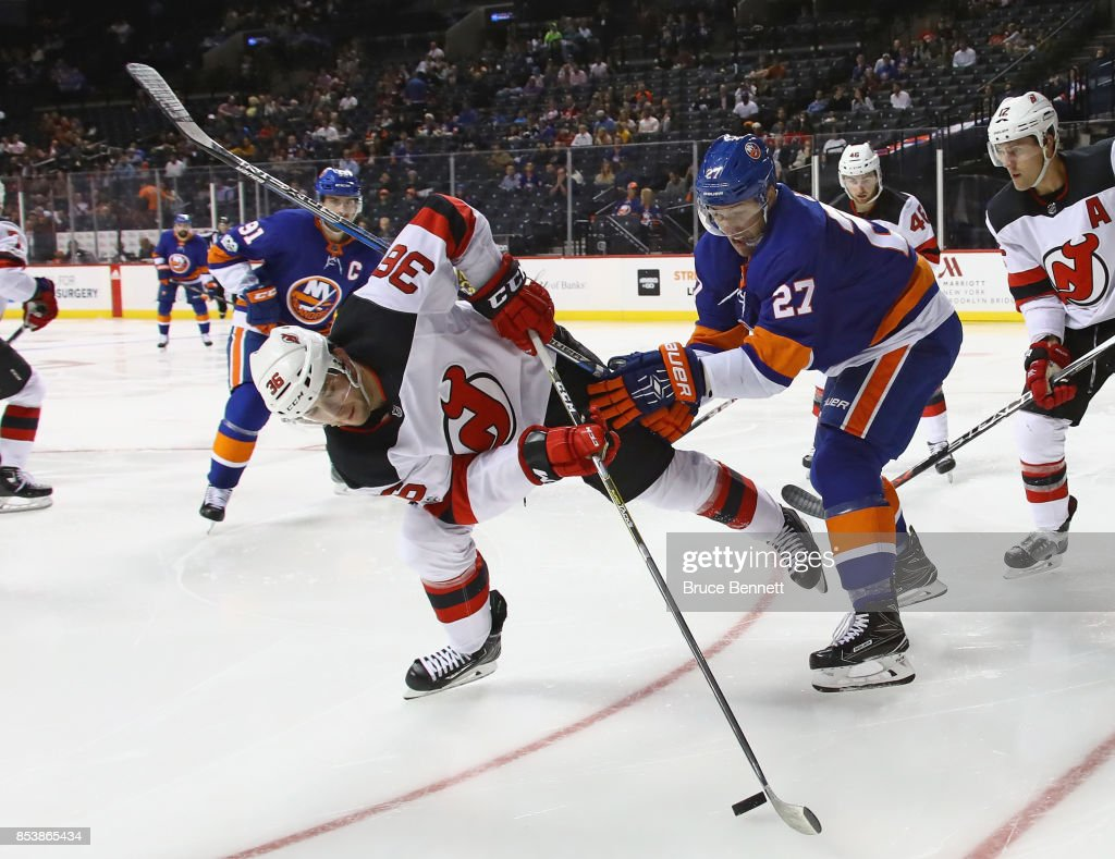 Anders Lee #27 of the New York Islanders knocks Stefan Noesen #23 of the New Jersey Devils off the puck in the second period during a preseason game at the Barclays Center on September 25, 2017 in the Brooklyn borough of New York City.