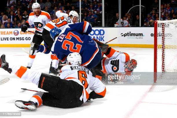 Anders Lee of the New York Islanders scores a goal past Carter Hart of the Philadelphia Flyers during the first period at NYCB Live's Nassau Coliseum...
