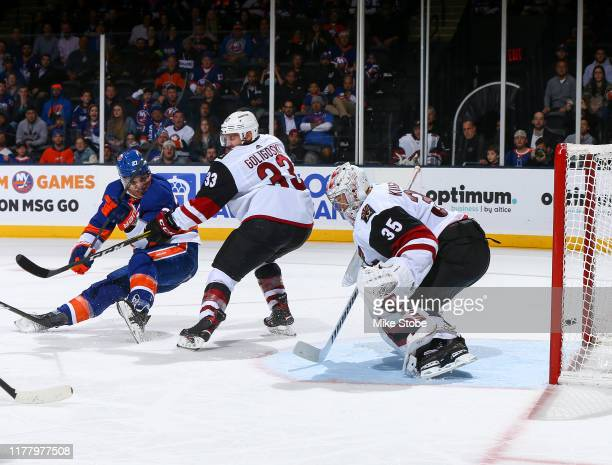 Anders Lee of the New York Islanders scores a goal past defender Alex Goligoski and Darcy Kuemper of the Arizona Coyotes at NYCB Live's Nassau...