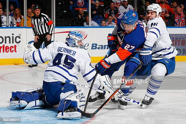 Anders Lee of the New York Islanders under pressure from Roman Polak of the Toronto Maple Leafs scores a first period goal past Jonathan Bernier of...