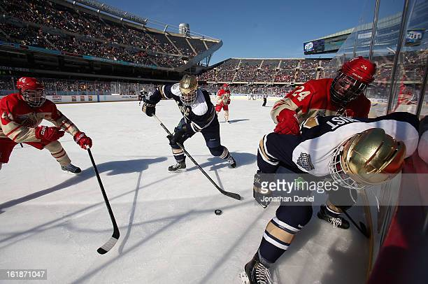 Anders Lee of the Notre Dame Fighting Irish tries to clear the puck past teammate Bryan Rust and Steven Spinell and Garrett Kennedy of the Miami...