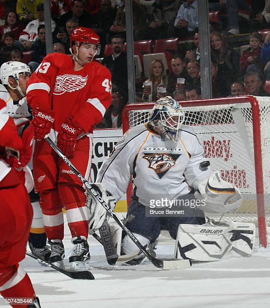 Anders Lindback of the Nashville Predators makes the save as Darren Helm of the Detroit Red Wings waits in front at the Joe Louis Arena on December 8...
