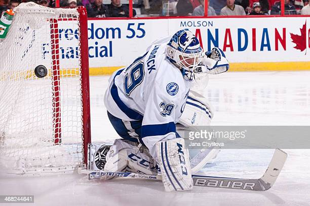 Anders Lindback of the Tampa Bay Lightning deflects the puck off his blocker during an NHL game against the Ottawa Senators at Canadian Tire Centre...
