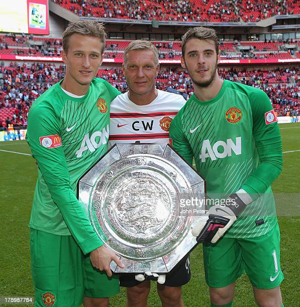 Anders Lindegaard Goalkeeping Coach Chris Woods and David de Gea of Manchester United pose with the FA Community Shield trophy after the FA Community...