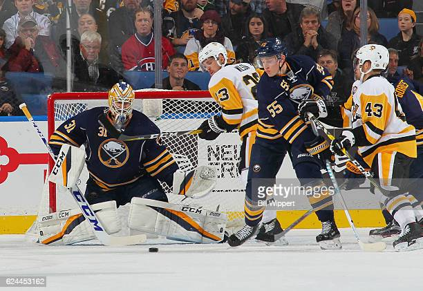 Anders Nilsson and Rasmus Ristolainen of the Buffalo Sabres defend against Scott Wilson and Conor Sheary of the Pittsburgh Penguins during an NHL...