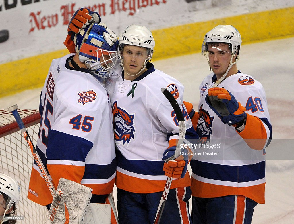 Anders Nilsson #45 of the Bridgeport Sound Tigers is congratulated by David Ullstrom #24 and Mike Halmo #40 after defeating the Manchester Monarchs during an American Hockey League game on December 29, 2012 at the Webster Bank Arena at Harbor Yard in Bridgeport, Connecticut.