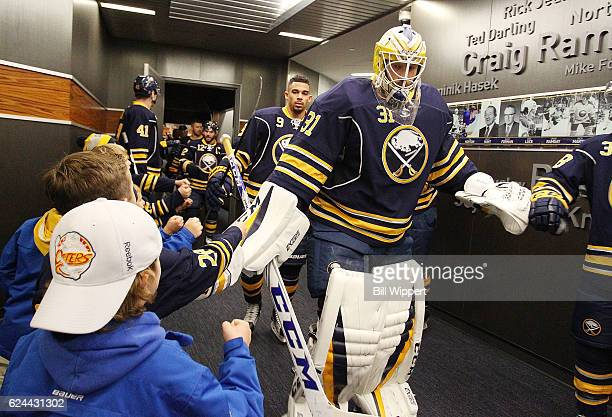 Anders Nilsson of the Buffalo Sabres greets young fans as he heads to the ice before an NHL game against the Pittsburgh Penguins at the KeyBank...