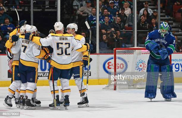 Anders Nilsson of the Vancouver Canucks looks on dejected as the Nashville Predators celebrate a goal during their NHL game at Rogers Arena December...