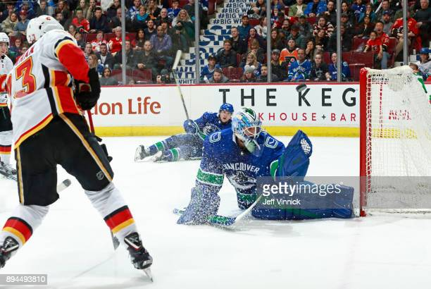 Anders Nilsson of the Vancouver Canucks makes a save off the shot of Sean Monahan of the Calgary Flames during their NHL game at Rogers Arena...