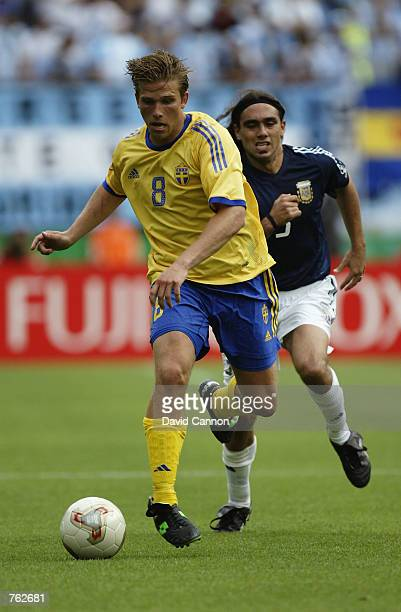 Anders Svensson of Sweden takes the ball past Juan Sorin of Argentina during the FIFA World Cup Finals 2002 Group F match played at the Miyagi...