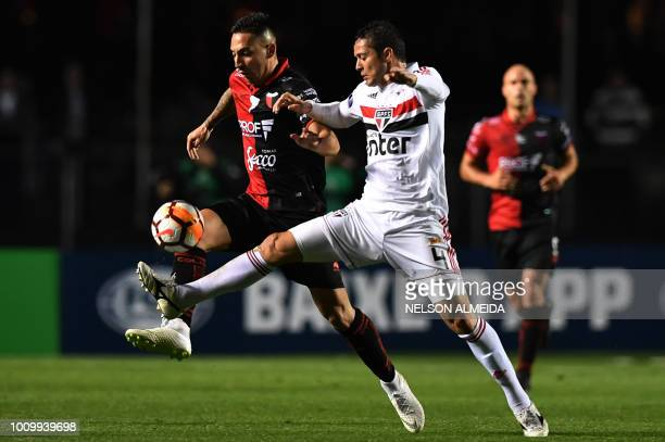 Anderson Martins of Brazil's Sao Paulo vies for the ball with Erik Godoy of Argentina's Colon de Santa Fe during their Copa Sudamericana football...