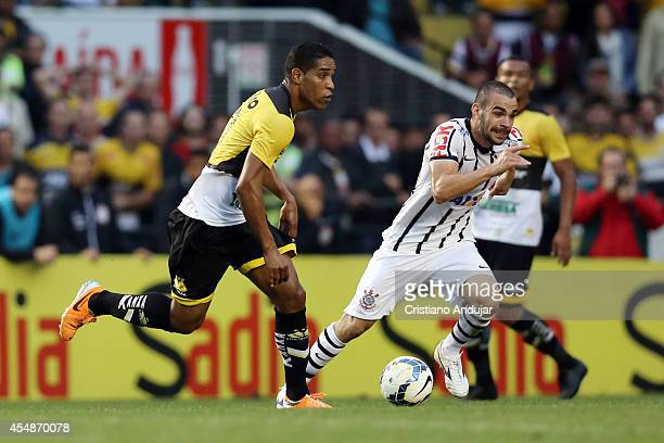 Anderson Martins of Corinthians try to stop Cleber Santana 10 of Criciuma during a match between Criciuma and Corinthians as part of Campeonato...