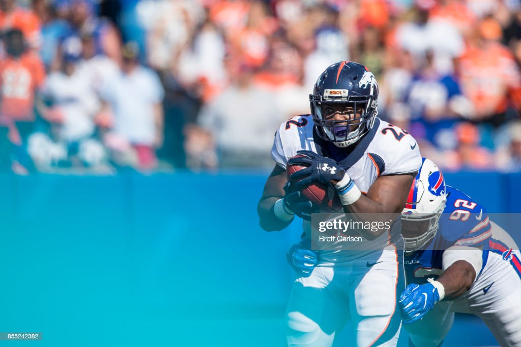 C.J. Anderson #22 of the Denver Broncos carries the ball as Adolphus Washington #92 of the Buffalo Bills brings him down during the second half on September 24, 2017 at New Era Field in Orchard Park, New York. Buffalo defeats denver 26-16.
