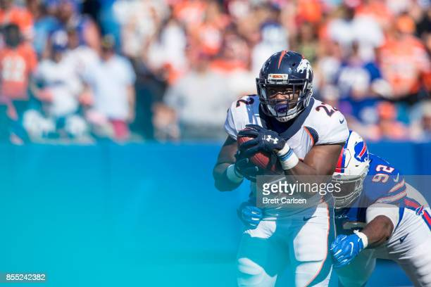 J Anderson of the Denver Broncos carries the ball as Adolphus Washington of the Buffalo Bills brings him down during the second half on September 24...