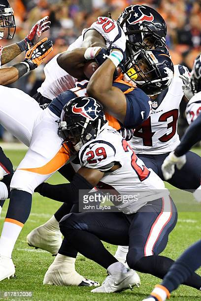 Anderson of the Denver Broncos is tackled by Andre Hal of the Houston Texans and Jadeveon Clowney during the first quarter on Monday, October 24,...