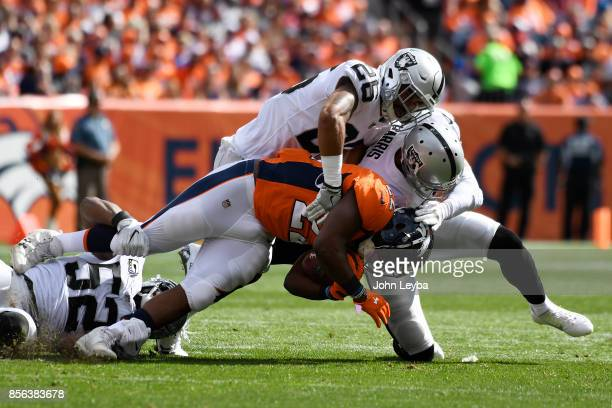 J Anderson of the Denver Broncos is tackled by Erik Harris and Shalom Luani of the Oakland Raiders in the first quarter The Denver Broncos hosted the...