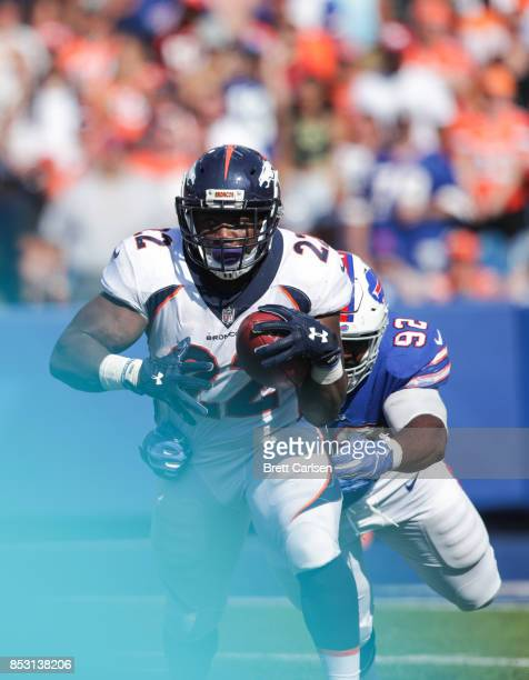 J Anderson of the Denver Broncos runs the ball as Adolphus Washington of the Buffalo Bills attempts to tackle him during an NFL game on September 24...