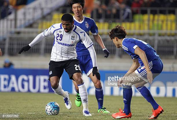 Anderson Patric Aguiar Oliveira of Gamba Osaka competes for the ball with Min Sang-Gi of Suwon Samsung Bluewings during the AFC Champions League...