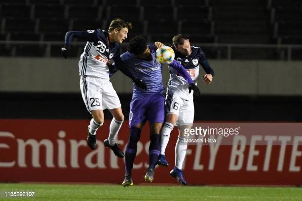 Anderson Patric Aguiar Oliveira of Sanfrecce Hiroshima competes for the ball against Anthony Lesiotis and Leigh Broxham of Melbourne Victory during...