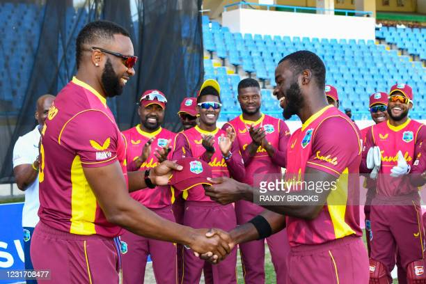 Anderson Phillip receives his debut cap from Kieron Pollard of West Indies at the start of the 3rd and final ODI match between West Indies and Sri...