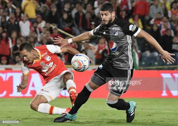 Anderson Plata of Santa Fe struggles for the ball with Matias De Los Santos of Millonarios during a match between Independiente Santa Fe and...